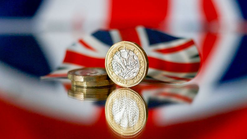 sterling coins in front of a British Union flag