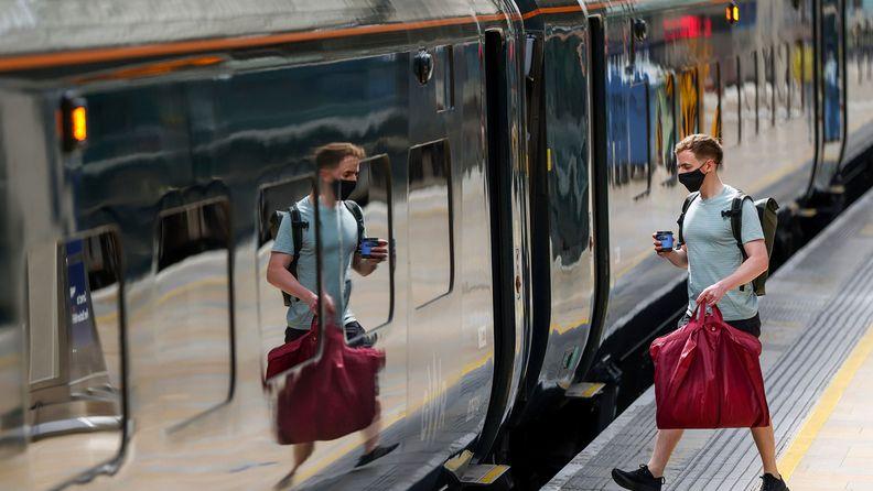 A commuter boards a Great Western Railway train at London Paddington railway station in London