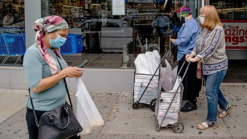 Pedestrians wearing protective masks walk along a street in the Midwood neighborhood in Brooklyn on Sept. 24, 2020