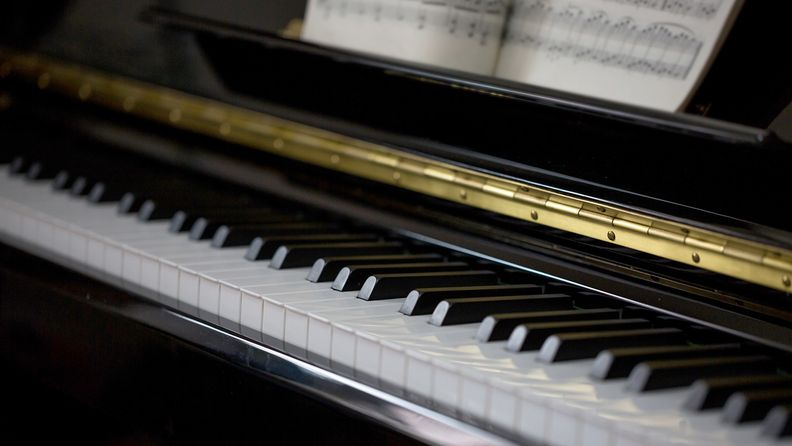 keyboard of a grand piano with music sheets