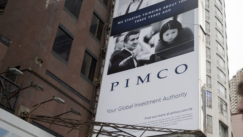 A Pacific Investment Management Co. advertisement is displayed on a building in Hong Kong