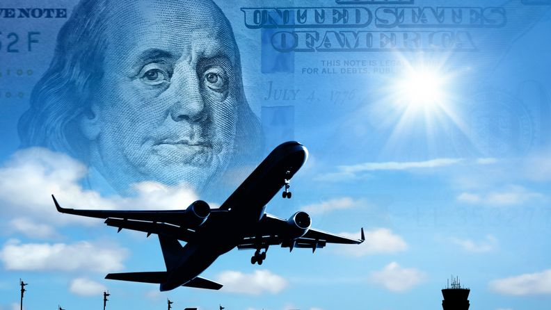 Silhouetted flying airplane over conceptual orange color sunset sky with Hundred dollar bill
