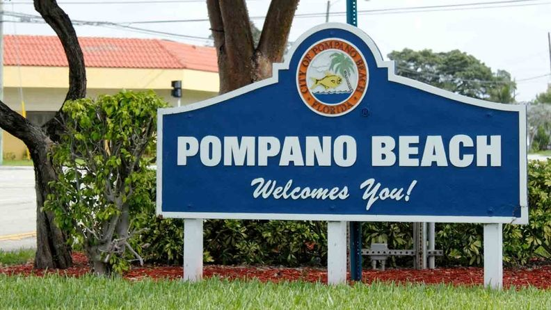 Large white and blue welcome sign at the entrance to the City of Pompano Beach, Fla.