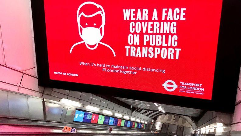 Huge Digital display screen advice during coronavirus pandemic as escalator descends to the underground train network.