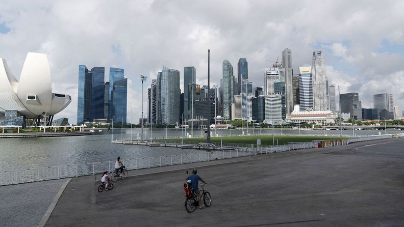 Cyclists ride along Marina Bay as the Artscience Museum, left, and buildings stand in the Central Business District in Singapore on July 6, 2020.