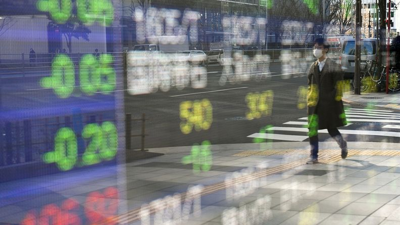 A pedestrian wearing a protective mask is reflected in an electronic stock board outside a securities firm in Tokyo on Jan. 4, 2021