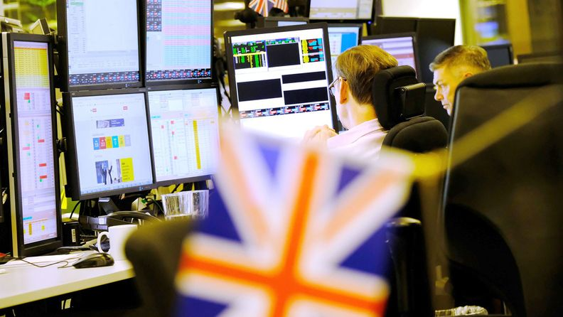 Traders monitor financial data on computer screens as they work on the trading floor at ETX Capital in London