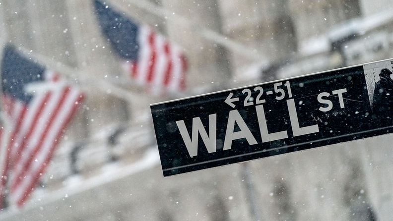 Wall Street street sign with the New York Stock Exchange in the background during a snowstorm