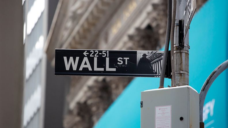 A Wall Street street sign is displayed in front of the New York Stock Exchange on Feb. 11, 2021