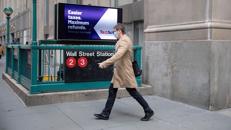 A pedestrian wearing a protective mask passes in front of a Wall Street subway station near the New York Stock Exchange on Jan. 4, 2021