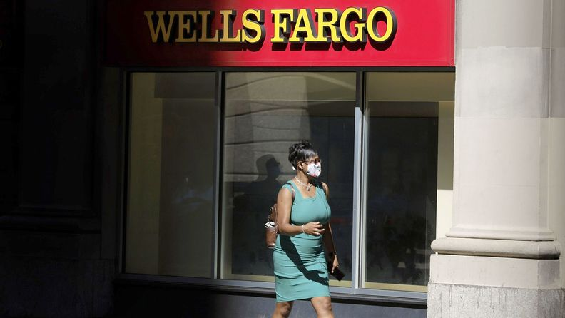 A pedestrian wearing a protective mask walks past a Wells Fargo & Co. bank branch in New YorK