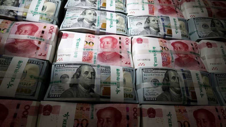 Bundles of Chinese 100 yuan banknotes and U.S. $100 banknotes arranged for a photograph